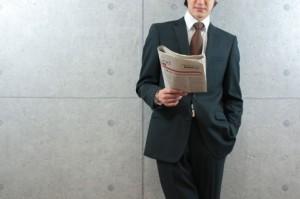 新聞を読むスーツの男性