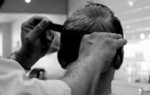 床屋で髪を切られる男性