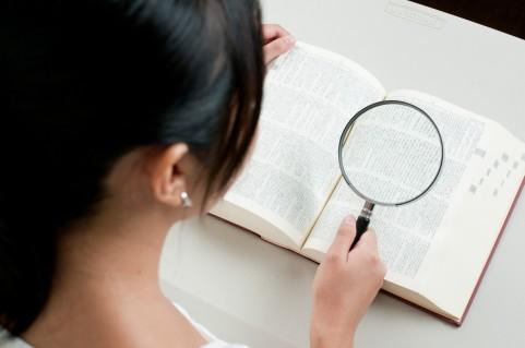 女性を虫眼鏡で調べる女性