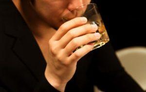 ウイスキーのグラスを持つ男性