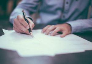 高級ボールペンでサインする男性