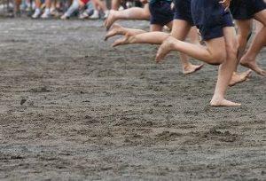 裸足でかけっこする小学生