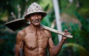 裸で畑仕事をする老人