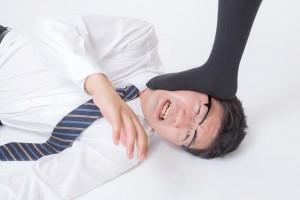 靴下に踏みつけられる男性