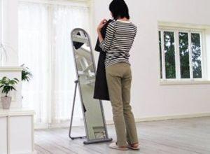 鏡の前で洋服を合わせる女性
