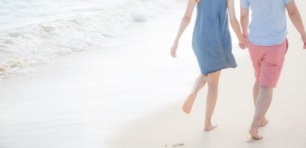 浜辺で手をつなぐカップル