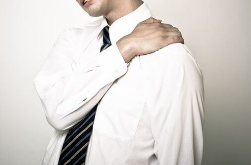 肩をおさえる男性