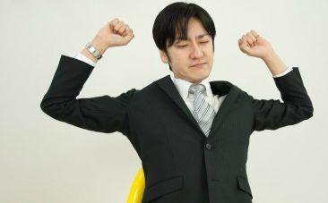 スーツ姿で背伸びする男性