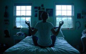 ベッドの上で瞑想する女性