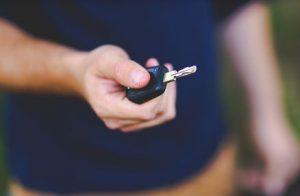 車のキーをもつ男性